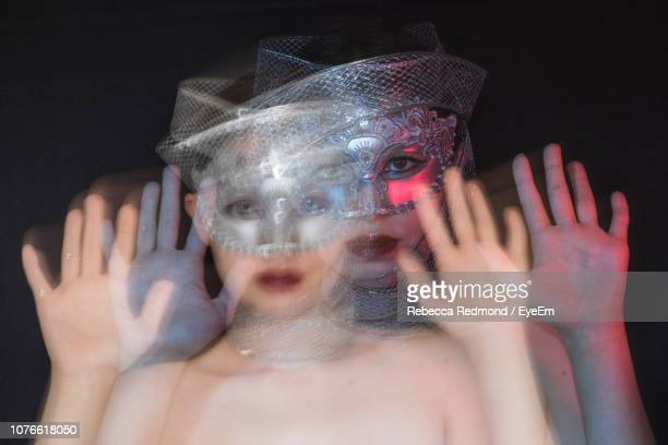 blurred motion of woman wearing mask against black background - black mask disguise stock pictures, royalty-free photos & images