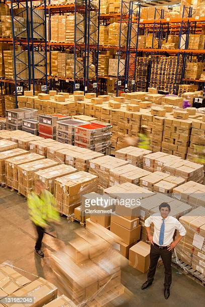 Blurred motion of workers working in warehouse while manager standing with hand on hip