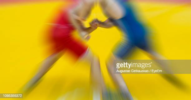 blurred motion of wrestlers fighting in health club - wrestling stock pictures, royalty-free photos & images