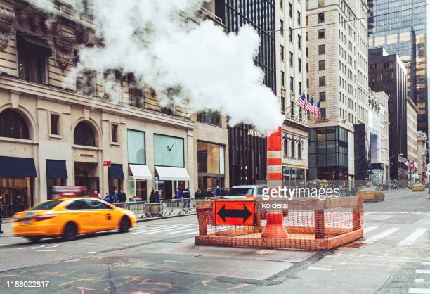 blurred motion of yellow taxi on fifth avenue - イエローキャブ ストックフォトと画像