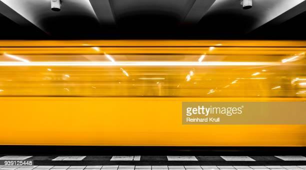 blurred motion of yellow train at night - u bahnstation stock-fotos und bilder