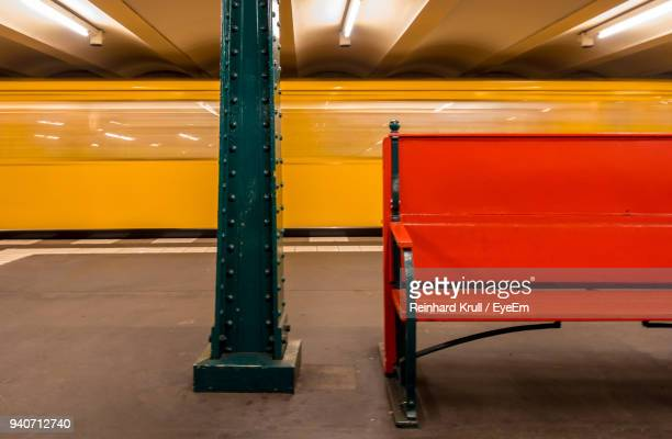 blurred motion of yellow train by red bench at subway station - banco asiento fotografías e imágenes de stock
