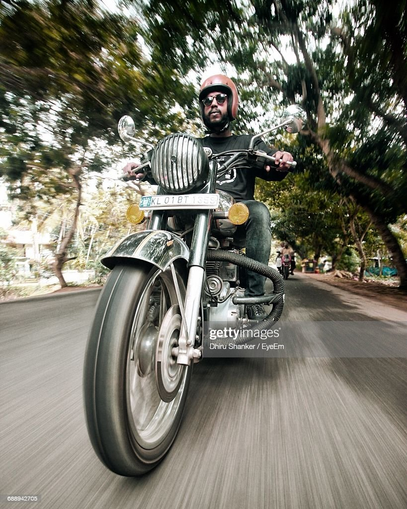 Blurred Motion Of Young Man Riding Motorcycle On Road : Stock Photo