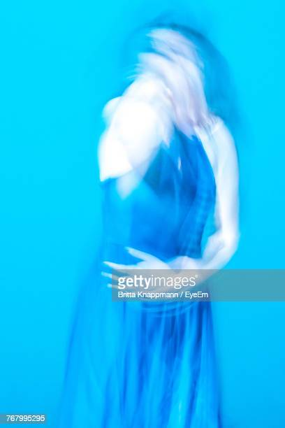 Blurred Motion Of Young Woman Against Blue Background