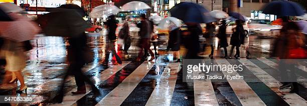 Blurred Motion On People With Umbrellas Walking On Zebra Crossing