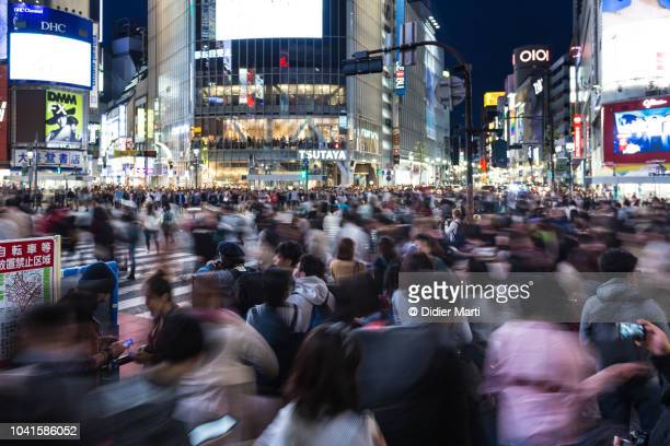 blurred motion on shibuya crossing in tokyo, japan - 人口爆発 ストックフォトと画像