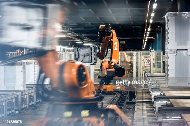 blurred motion photo of robotic arms in a factory - robotic arm stock pictures, royalty-free photos & images