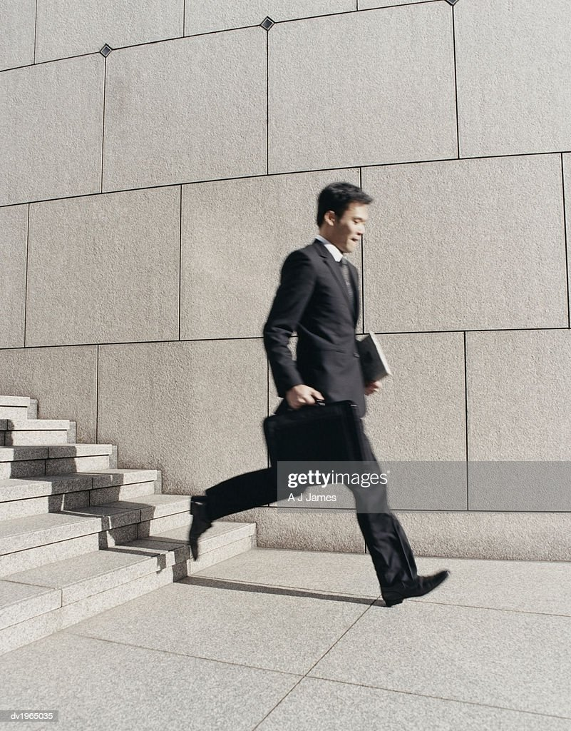 Blurred Motion Shot of a Businessman Descending Stone Steps : Stock Photo