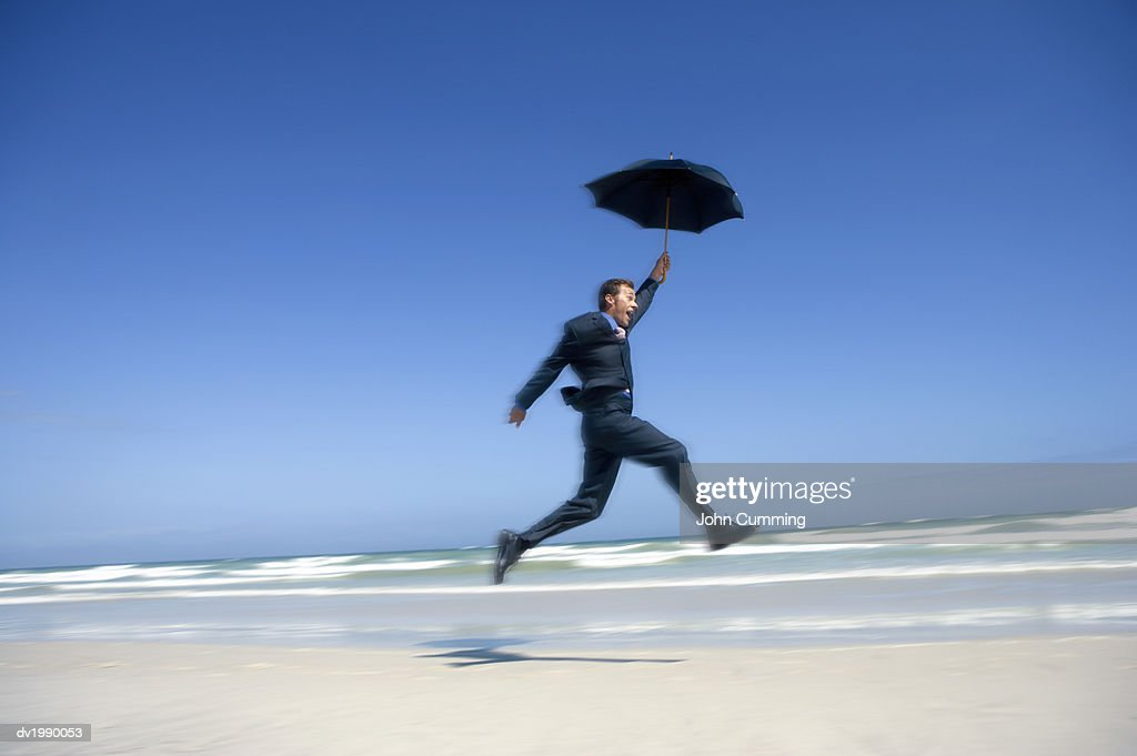 Blurred Motion Shot of a Care Free Businessman Jumping in Mid Air, on a Beach : Stock Photo