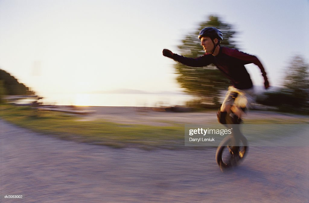 Blurred Motion Shot of a Man Riding a Monocycle : Stock Photo