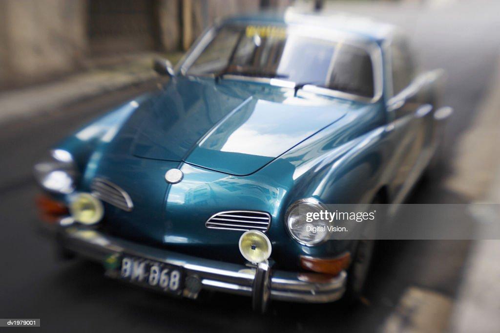 Blurred Motion Shot of a Metallic Blue Classic Car : Stock Photo