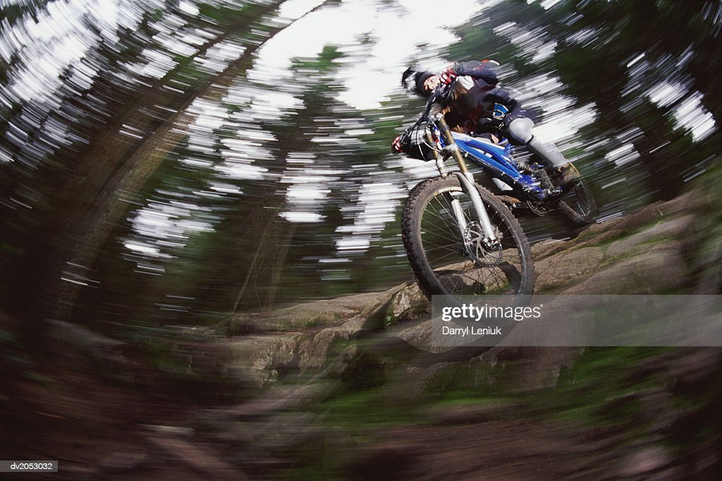 Blurred Motion Shot of a Mountain Biker in a Forest : Stock Photo