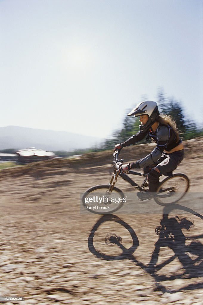 Blurred Motion Shot of a Woman Riding a BMX on a Dirt Track : Stock Photo