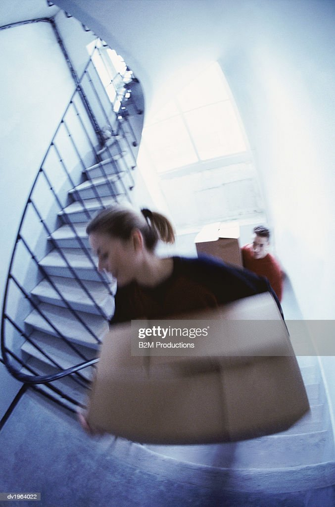 Blurred Motion Shot of a Young Couple Carry Cardboard Boxes Up a Staircase : Stock Photo