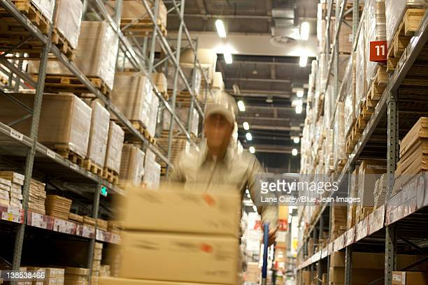 Blurred motion shot of Chinese warehouse worker pushing boxes