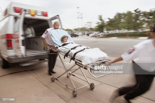 blurred motion shot of emts wheeling gurney with patient away from ambulance - hospital gurney stock pictures, royalty-free photos & images