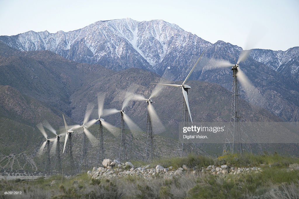 Blurred Motion Shot of Nine Revolving Wind Turbines : Stock Photo