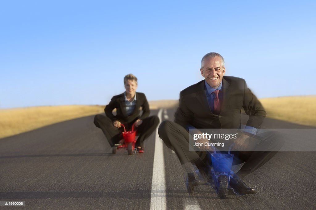 Blurred Motion Shot of Two Business Executives Riding Small Tricycles : Stock Photo