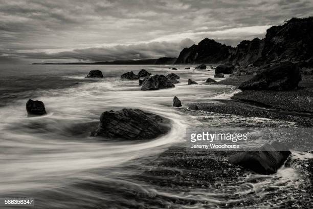 Blurred motion view of waves on rocky beach