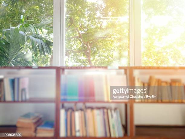 blurred of books on bookshelves with green leaves background in the public library. - aungsumol stock pictures, royalty-free photos & images