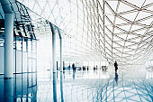 Blurred people entering modern architecture