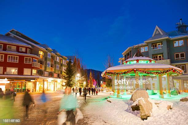 blurred people in a snowy village in whistler - whistler british columbia stock pictures, royalty-free photos & images