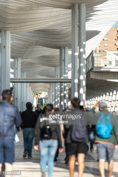 blurred people in the foregrund under the white pergola in málaga's port area - dorte fjalland stock-fotos und bilder