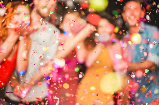 Blurred people making party throwing confetti - Young people celebrating on weekend night - Entertainment, fun, new year's eve, nightlife and fest concept - Defocused photo 1071000086