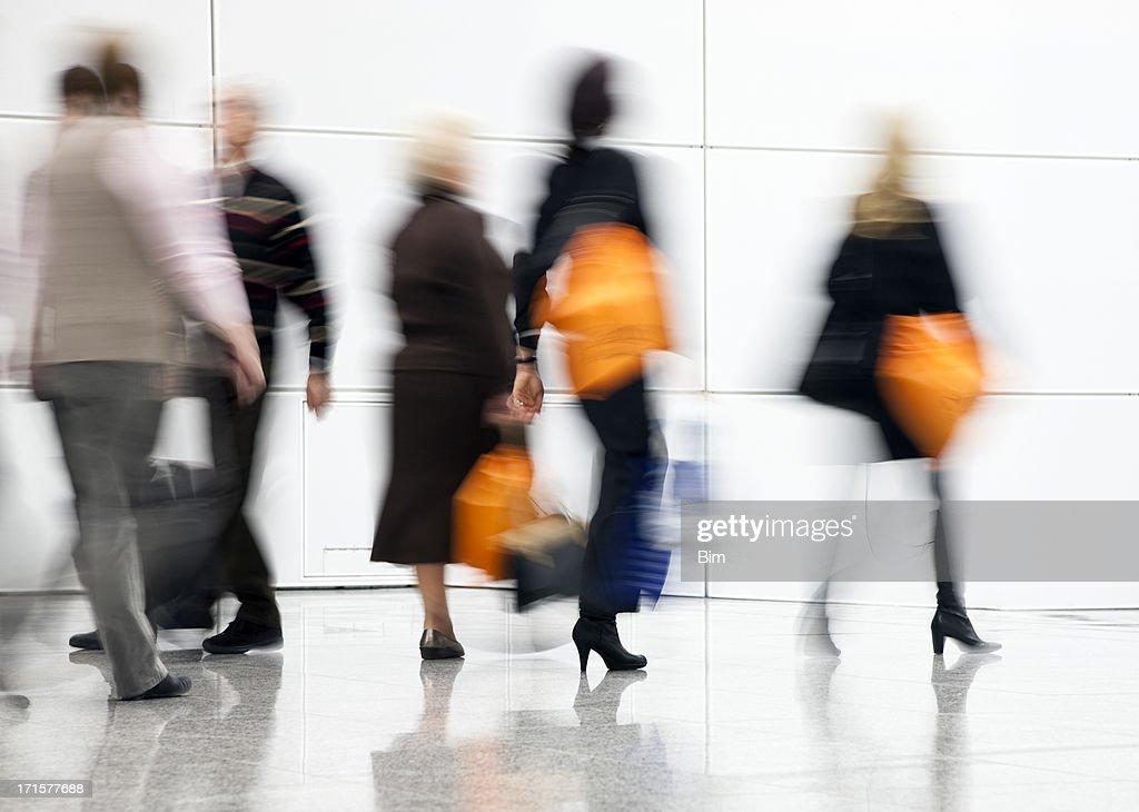 Blurred People Rushing Down Corridor, Women Carrying Shopping Bags : Stock Photo