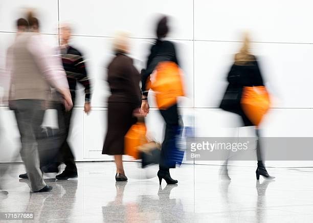 Blurred People Rushing Down Corridor, Women Carrying Shopping Bags