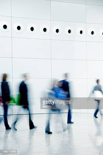 Blurred People Walking Down a Hallway