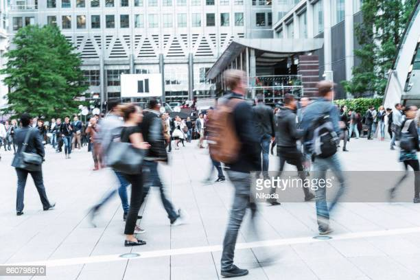 blurred people walking in front of modern office buildings - london financial district stock photos and pictures
