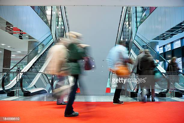 Blurred People Walking Red Carpet to Escalator in Modern Interior