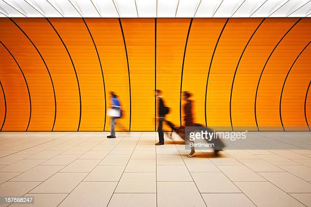 Blurred people walking with luggage in an orange tunnel
