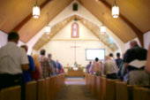 Blurred Photo of the Iterior of a Church Sanctuary with Congregation, Pastor, and a Large Cross Visible