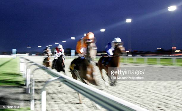 Blurred picture of horses running down the track during an evening race meeting in the dark at Kempton Park race course in London England UK