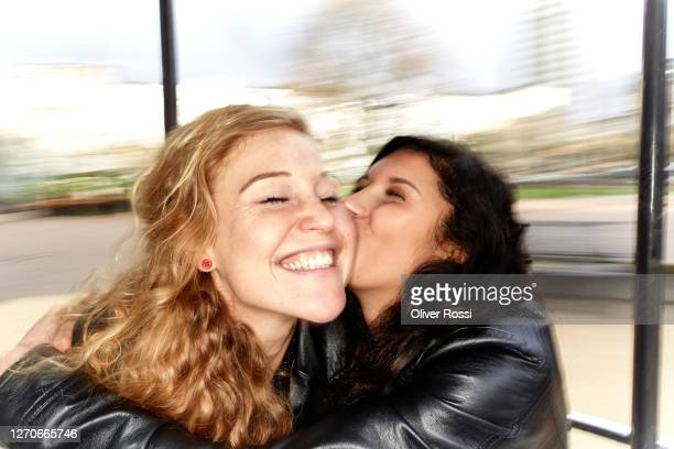 blurred portrait of two happy young women hugging and kissing - image focus technique stock pictures, royalty-free photos & images