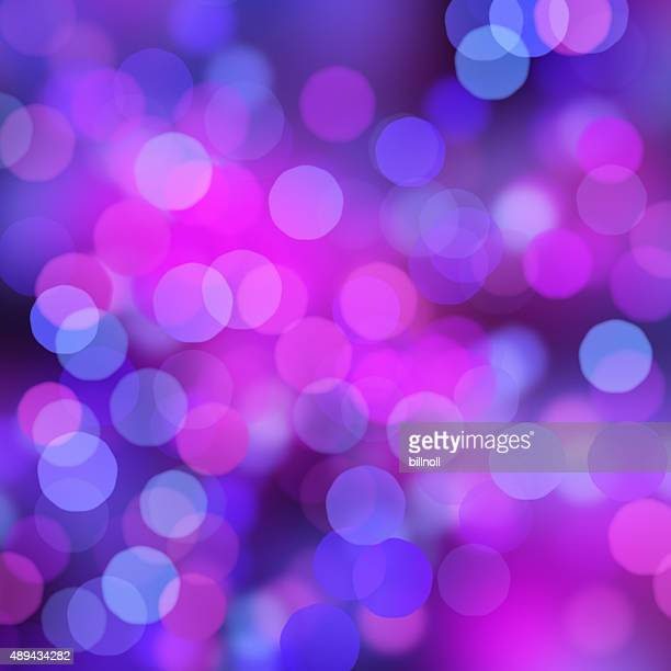 Blurred purple and blue bokeh dots on black background