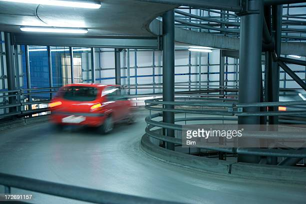 Blurred Red Car in Spiral Exit from Parking Garage