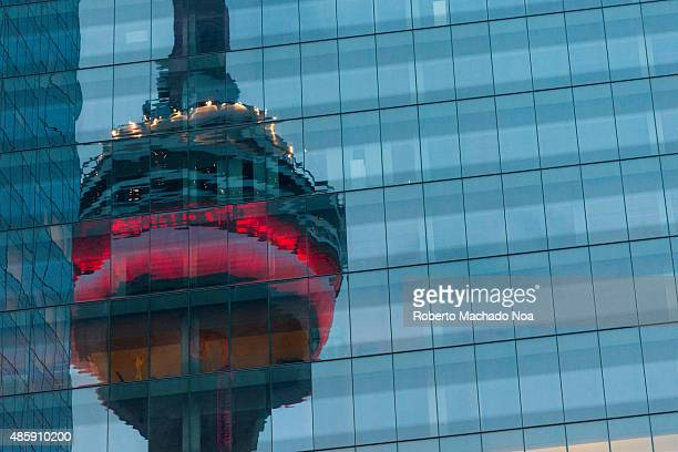 WEST TORONTO ONTARIO CANADA Blurred reflection of the CN tower on the exterior of a glass facade building in the eveningThe CN Tower is a 55333 meter...