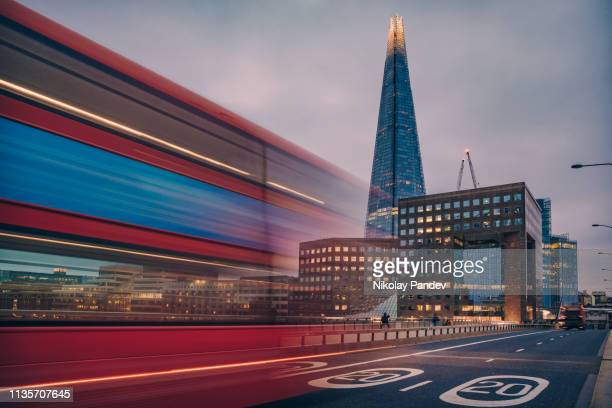 blurred road traffic motion on london bridge with the shard building as background - toned stock image - motion stock pictures, royalty-free photos & images