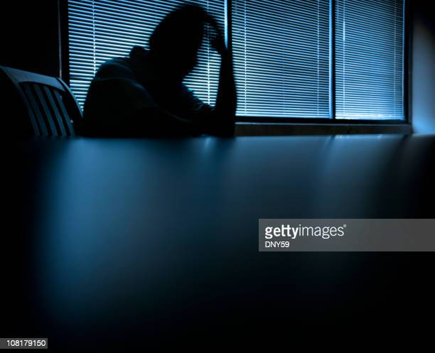 Blurred Shadow of Man Holding Head at Table