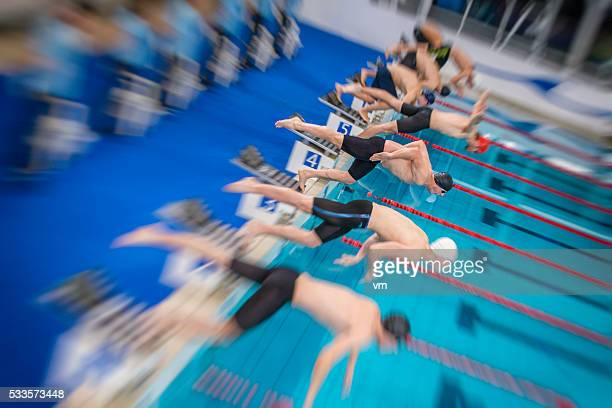 Blurred shot of professional swimmers jumping into a pool