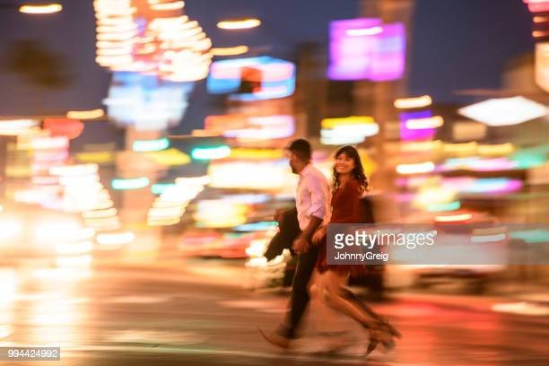 blurred shot of young couple crossing road at night - fremont street las vegas stock pictures, royalty-free photos & images