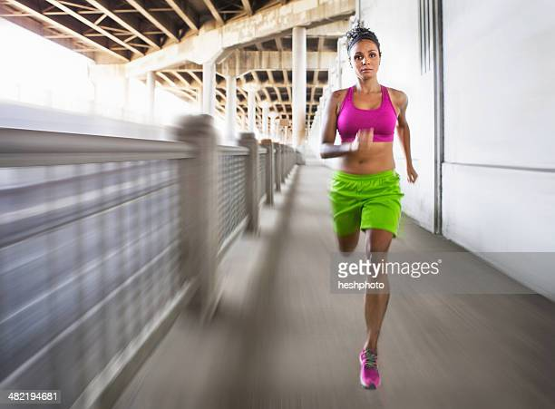 blurred shot of young woman running on urban bridge - heshphoto photos et images de collection