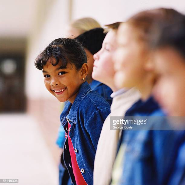 blurred side profile of a girl (8-10) sticking out of a line of children at school