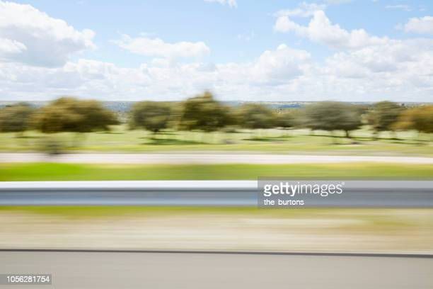 blurred sideview out of car`s window on crash barrier and landscape on a motorway - leitplanke stock-fotos und bilder