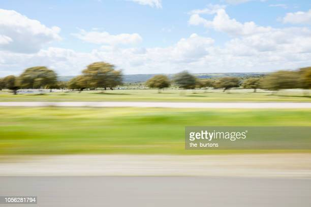 blurred sideview out of car`s window on crash barrier and landscape on a motorway - rushing the field stock pictures, royalty-free photos & images