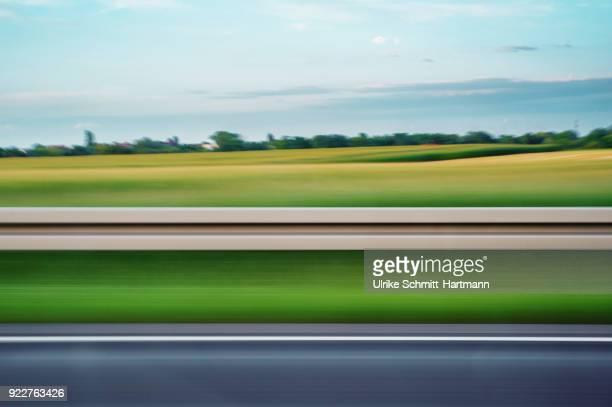 blurred sideview out of car's window on fields - leitplanke stock-fotos und bilder