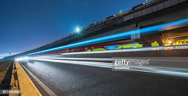 blurred traffic light trails on road - in a row stock pictures, royalty-free photos & images